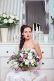 Wedding. Bride in beautiful dress sitting on sofa indoors in white studio interior like at home. Trendy wedding style Royalty Free Stock Photo