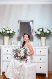 Wedding. Bride in beautiful dress sitting on sofa indoors in white studio interior like at home. Trendy wedding style Royalty Free Stock Photos