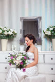 Wedding. Bride in beautiful dress sitting on sofa indoors in white studio interior like at home. Trendy wedding style Royalty Free Stock Images