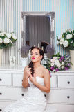Wedding. Bride in beautiful dress sitting on sofa indoors in white studio interior like at home. Trendy wedding style Stock Image