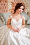 Wedding. Bride in beautiful dress sitting on sofa indoors in white studio interior like at home. Trendy wedding style. Wedding. Bride in beautiful dress sitting Royalty Free Stock Images