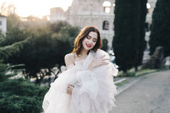Wedding bride fineart outside Rome colosseum sunset. Fine art boho wedding destination Italy park street dress Royalty Free Stock Photography