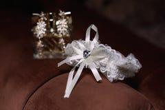 Wedding bride garter and gold earrings Stock Photo
