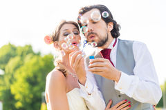Wedding bride and groom blowing bubbles Stock Photos