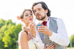 Wedding bride and groom blowing bubbles outside on field Stock Image