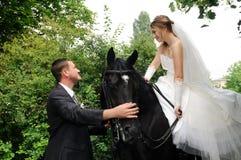 Wedding bride and groom on horseback Royalty Free Stock Photography