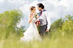 Wedding bride and groom in a meadow, with bridal bouquet Stock Photo