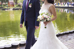 Wedding. The bride and groom near the river. Wedding outfit and bouquet. Royalty Free Stock Photo
