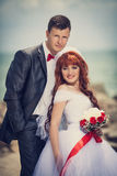 Wedding: bride and groom by the sea. Newlyweds on plyazhe.Buket bride with a red ribbon, the groom with a red bow tie. Red-haired Bride Stock Image