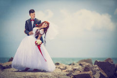 Wedding: bride and groom by the sea. Newlyweds on plyazhe.Buket bride with a red ribbon, the groom with a red bow tie. Red-haired Bride Royalty Free Stock Photo