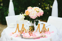 Wedding Bride Groom Table. A romantic garden wedding reception bride and groom table with a pink and gold color scheme. Peony bouquet centerpiece. Rope tying Stock Photography