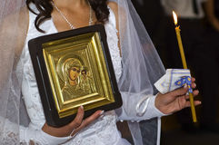Wedding, bride, an icon. Bride during the wedding ceremony, holding an icon and a candle, a beautiful church ceremony, during which time the priest reads the Stock Image