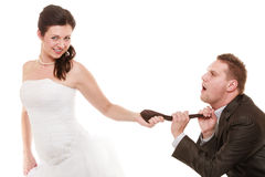 Wedding. Bride pulling tie of groom. Emancipation. Emancipation. Humorous funny wedding couple bride and groom isolated. Woman pulling the tie of man, wife royalty free stock photos