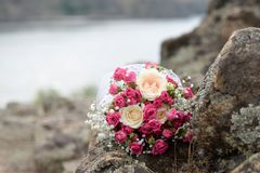 Wedding bride`s bouquet of pink and white flowers roses lies on a log by the lake . wedding background with copy space royalty free stock photography