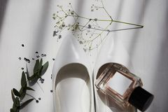 Wedding bride`s elements on white striped background. Wedding bride`s elements such as shoes and perfume on the table on the striped background stock photography