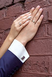 Wedding. Bride's hand rests on the groom's hand. Just married couple's hands together. Family couple's hands with rings and a cuffling next to the brick wall Royalty Free Stock Photography