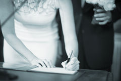 Wedding bride signing marriage register Stock Images