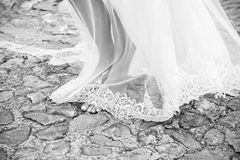 Wedding bride taking a walkk berefoot. In the park on the rocky yard Stock Photography
