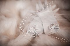 Wedding Bride white gloves with a bow on each finger on fur with pearls and veil, morning of the bride, wedding accessories. Beautiful Wedding Bride white gloves Royalty Free Stock Photography