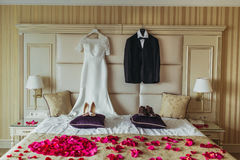 Wedding brides drees and grooms suit hang on the bad with shoes and decorative petals. Of flowers Royalty Free Stock Photo