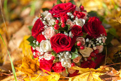 Wedding bunch of flowers lies on fallen leaves. Stock Photos