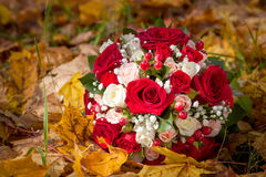 Wedding bunch of flowers lies on fallen leaves. Royalty Free Stock Photography