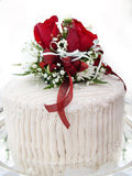Wedding cake. Red roses and flowers atop wedding cake Stock Image