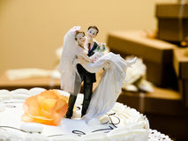 Wedding cake. With a bride and bridegroom and blurred gifts in the background Stock Photos