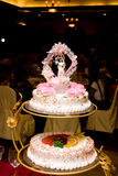 Wedding cake. Traditional three layer wedding cake decorated with flowers and a bride and groom ornament on top Stock Image