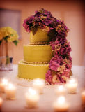 Wedding cake. A tiered wedding cake in green covered with purple flowers and surrounded by candles stock photography