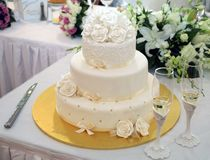 Wedding cake. White wedding cake on a gold plate Stock Images