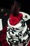 Wedding cake. A tiered wedding cake in black and white with red roses and a peacock feather top stock images