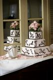 Wedding Cake. A wedding cake with pink roses sitting on a shelf with a mirror. A good place for text on the bottom right side of the photo Royalty Free Stock Image