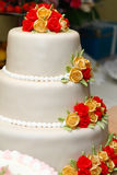 Wedding cake. Three-tiered round wedding cake covered in white rolled fondant and decorated with brightly colored roses Stock Images