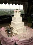 Wedding Cake. White wedding cake sits on pink table along with champagne flowers and flutes Royalty Free Stock Images