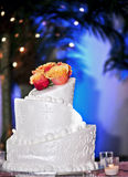Wedding cake. A tiered wedding cake in with roses on top and surrounded by candles stock photos