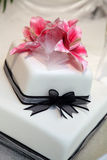 Wedding cake. White wedding cake with black ribbon and pink lily Stock Photo