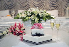 Wedding cake. White wedding cake with black ribbon and pink lily Royalty Free Stock Photography