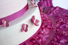 Wedding cake. Decorated with rose petals and butterflies stock photos