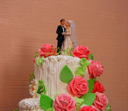 Wedding cake. The upper part of the traditional wedding cake with bride and groom figurines Stock Photo