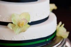 Wedding cake. White wedding cake with black ribbon and flowers Stock Images