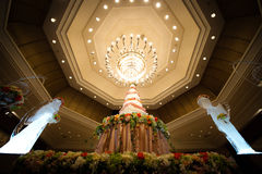 Wedding cake. With Chandeliers in hotel ballroom Stock Images