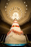 Wedding cake. With Chandeliers in hotel ballroom Royalty Free Stock Images