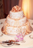 Wedding cake. Three tiered wedding cake and champagne glasses on a table royalty free stock images