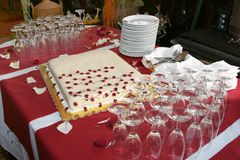 Wedding cake. With plates and glasses on a red background Stock Images