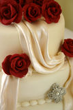 Wedding Cake. White wedding cake with sugar craft red roses Stock Photo