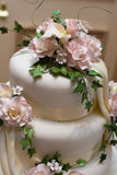 Wedding cake. With pink roses and green foliage icing Royalty Free Stock Photo