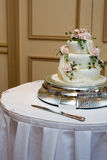 Wedding cake. With pink roses and green foliage icing on a table with a knife Royalty Free Stock Images