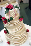 Wedding cake. A big wedding cake with red roses on it Stock Photos