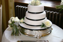 Wedding cake. Three tiered wedding cake and bridal bouquet Royalty Free Stock Image